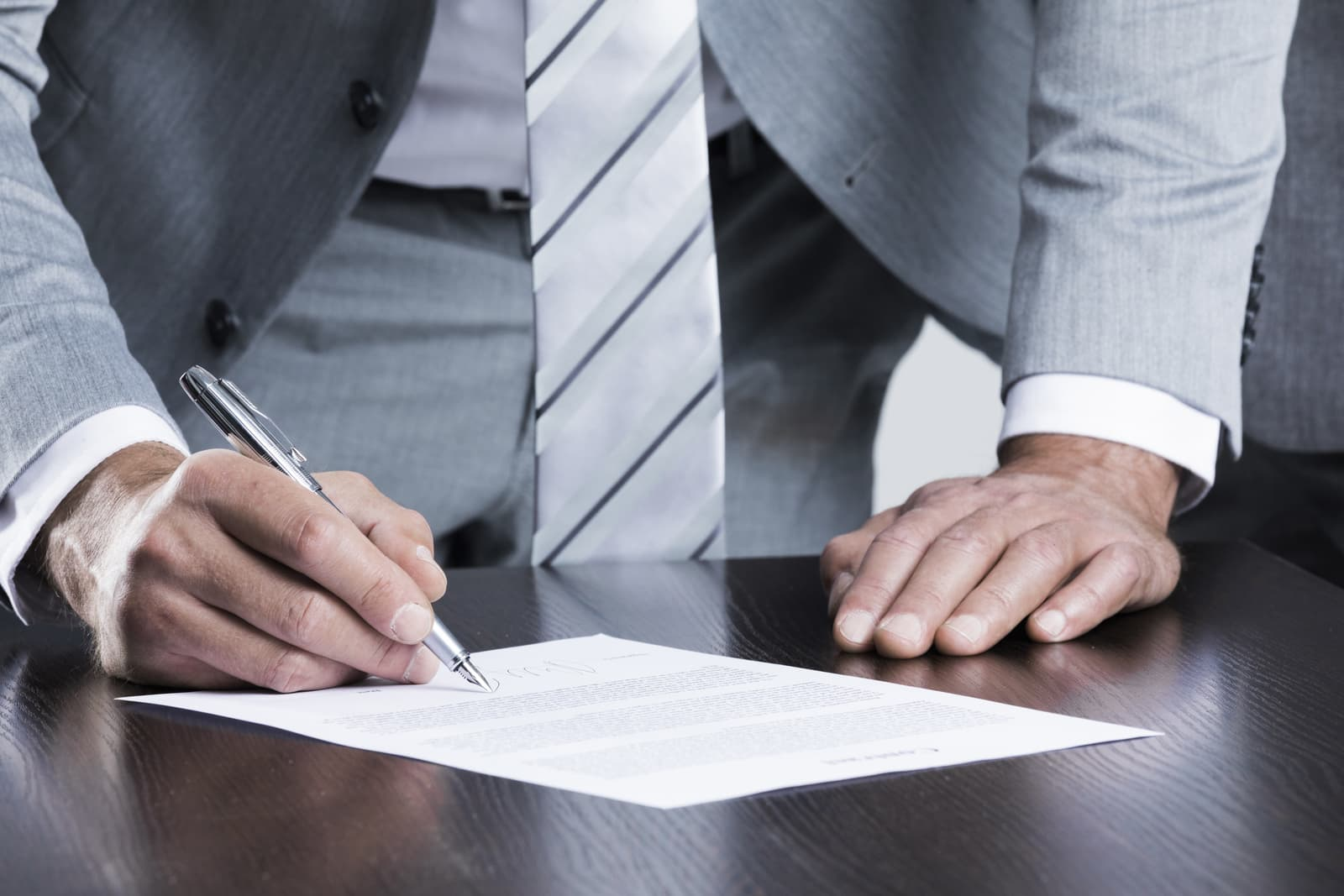 a man signing a document while standing