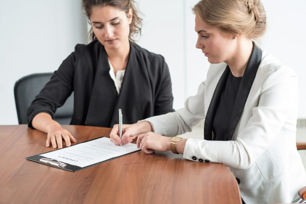 two women in suit with one of them writing a notary document