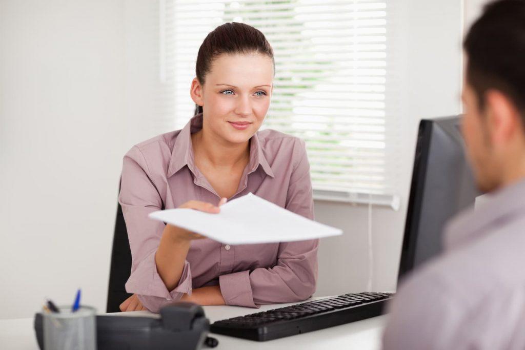 a woman handing a document