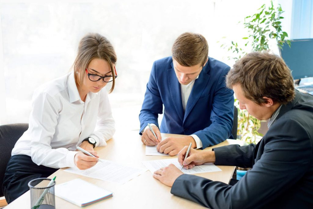 three people taking notes over a discussion