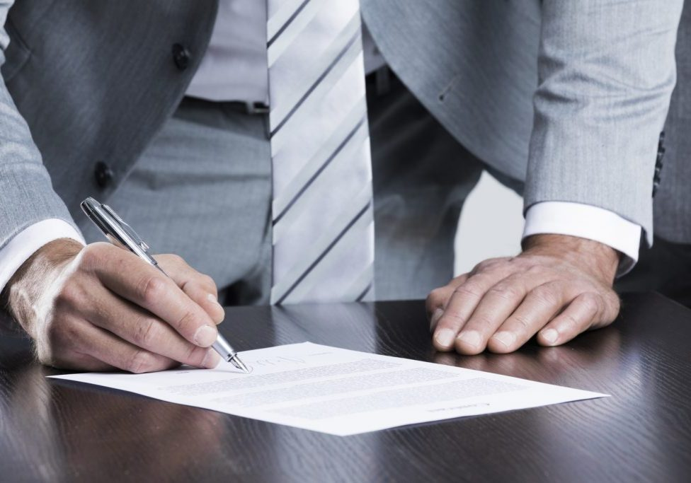 man signing on the paper